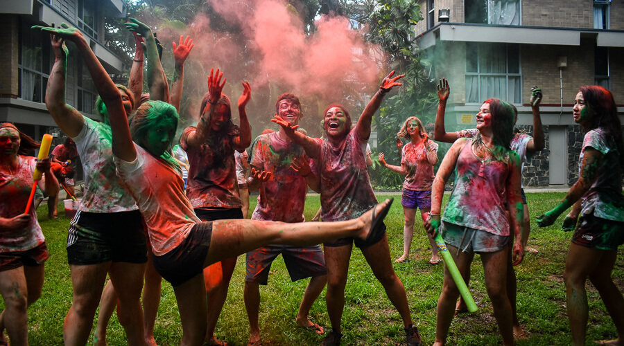 IH residents throwing coloured dye in the air covering themselves to celebrate Holi an Indian cultural festival